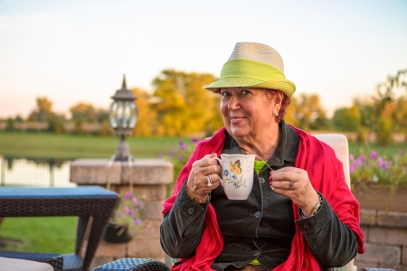 Senior woman with a straw green hat, sitting at the patio and showing her hot tea, perhaps she wants to stay warm photo