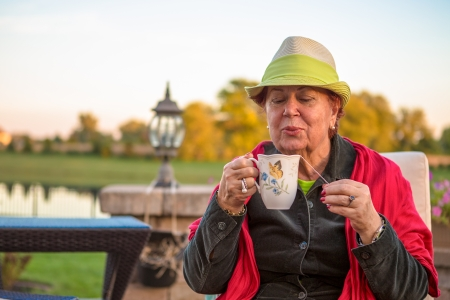 Senior woman with a straw green hat, sitting at the patio and blowing her hot tea, perhaps she wants to stay warm photo