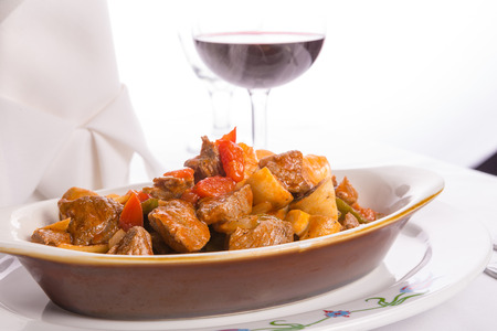 Beef Saute  with tomatoes, mushrooms and onions served in oval baking dish along with red wine photo