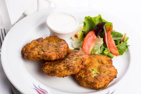 papas doradas: Vegeterian calabacín croquetas de patata servido en un plato blanco y decorado con verduras