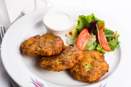 browns: Vegeterian zucchini hash browns served on a white plate and garnished with vegetables Stock Photo