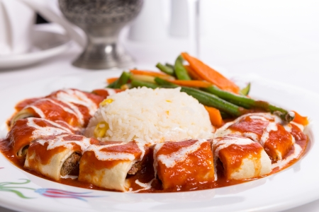 Turkish Beyti Kebap garnished with vegetables photo