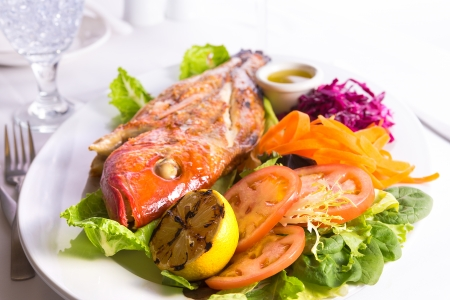 Full cooked tilapia fish served in a plate with vegetables and fish sauce complimented with Ice Water photo