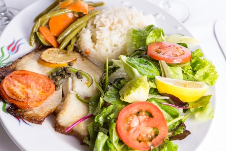 Tilapia fish cooked with capers, lemon and tomatoes and served in a plate with vegetables and pilaf rice photo
