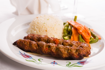 Turkish Adana Kebap with rice pilaf and vegetables served on a Plate Stock Photo