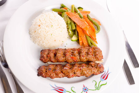 zesty: Turkish Adana Kebap with rice pilaf and vegetables served on a Plate Stock Photo