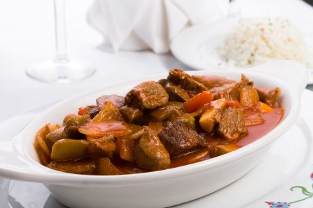 Beef stew with tomatoes, mushrooms and onions served in white oval baking dish