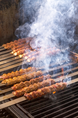 turkish kebab: Cooking Adana kebabs on the restaurant style grill, smoke  coming out from them that they might be ready Stock Photo
