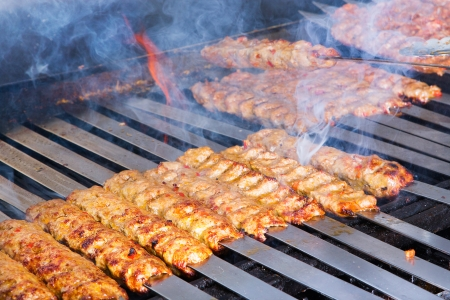 Cooking Adana kebabs on the restaurant style grill, smoke  coming out from them that they might be ready photo