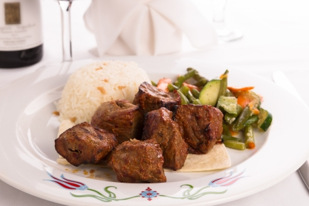 zesty: Macro shot of shish kebabs garnished with vegetables and rice pilaf, napkin and vine glass on the background Stock Photo