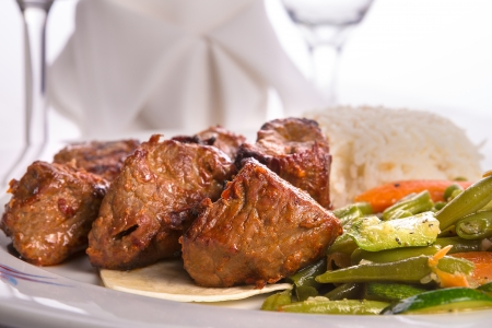 kabob: Macro shot of shish kebabs garnished with vegetables and rice pilaf, napkin and vine glass on the background Stock Photo