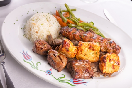 Mixed chicken, lamb adana shish kebabs served served on gyro doner with rice pilaf and garnished with green vegetables, photo
