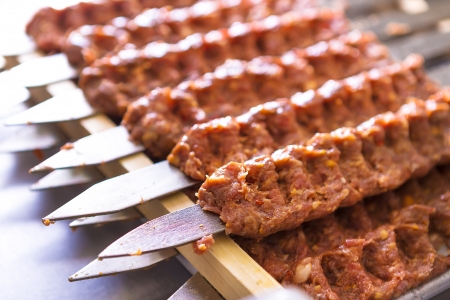 Several Adana Kebab skewers lined up waiting to be cooked and served