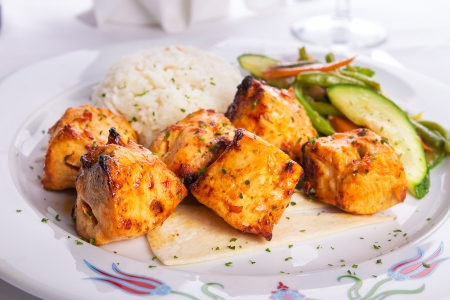 zesty: Zesty chicken shish kebabs served with rice pilaf on a tiny lavash bread garnished with cooked vegetables zucchini, green beans and carrots