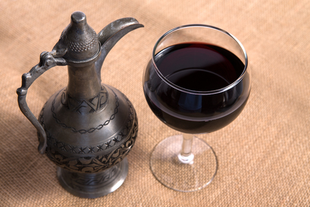 Simple View of pewter flagon and red wine in the glass on the burlap fabric Stock Photo