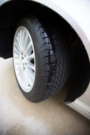 traction: Wet automobile tire, on a concrete pavement, treads are showing clearly with rain in them