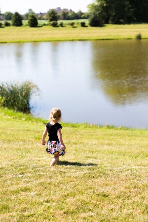 quite time: Little toddler girl walking on the newly cut grass by the pond peacefully, having quite time