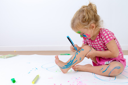 Cute toddler concentrated painting her legs carefully with colorful pens after she painted her face