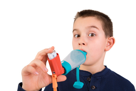 Nine years old kid with allergic asthma, inhaling his medication through spacer while looking at with his wide opened eyes perhaps he is getting energy boost Stock Photo
