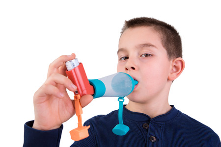 asma: Chico de nueve años de edad con asma alérgica, la inhalación de la medicación a través de espaciador mientras mira con sus ojos cansados