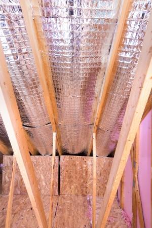 fiberglass: El trabajo continuo del aislante del ático con barrera térmica reflectora entre las vigas del ático y pared de la rodilla Foto de archivo