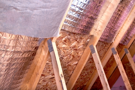 Inside gable and joist view of ongoing project, insulation of attic with fiberglass cold barrier and reflective heat barrier between the attic joists