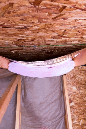 attic: Insulating of attic with fiberglass cold barrier and reflective heat barrier used as baffle between the attic joists, work is ongoing Stock Photo