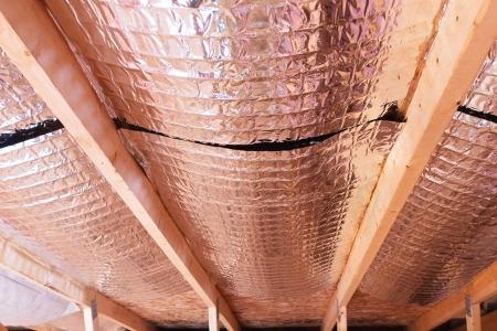 fiberglass: Aislante del ático con fibra de vidrio fría barrera y barrera térmica reflectante utilizado como tabique entre las vigas del ático para aumentar la ventilación para reducir la humidificación