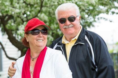 Easygoing positive senior couple posing with their sports clothing and sunglasses in front of blooming spring tree. Man holding his partners shoulder, seems like she enjoys it