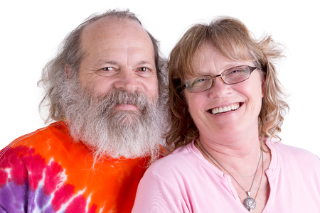 baby boomer: Happy baby boomer couple looking at you genuinly  and smiling, male have long beard and colorful tye dye t-shirt, isolated on white Stock Photo