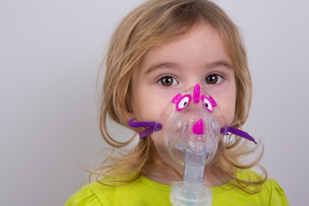 oxigeno: Chico de nueve años de edad con asma alérgica, la inhalación de la medicación a través de espaciador mientras mira con sus ojos cansados