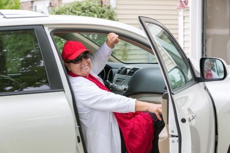 Senior lady with red hat sitting on the passenger seat getting ready close the door and hit the road, she has genuine smile on her face photo