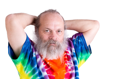 boomer: Senior male adult man holding his hair on the back casually and looking at you in his tie dye T-shirt Stock Photo