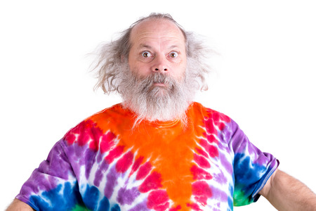 Cute grey long hair and beard senior man so surprised that his eyes came out, he is wearing a tie dye colorful T-shirt Stock Photo