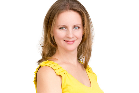 Portrait of genuinely smiling business woman, she is looking in to your eyes friendly in her yellow dress photo