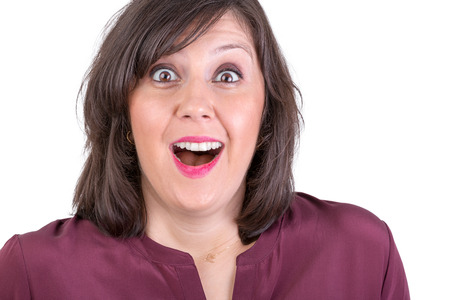 reveal: Happily amazed dark haired lady looking in to your eyes with her mouth wide open Stock Photo