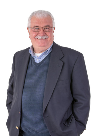 White hair senior adult with mustache looking at you smiling and satisfactorily with his glasses wearing dark blue suit