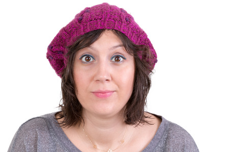 amused: Attractive woman wearing a purple knitted winter cap opening her eyes wide in astonishment and scepticism to show her disbelief, isolated on white