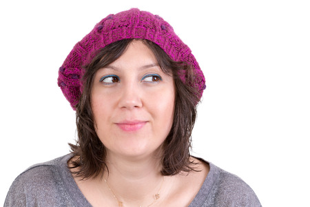 Thoughtful woman wearing a knitted purple winter cap smiling in anticipation of being able to realise her dreams, looking off with her eyes to the side and smiling, isolated on white photo