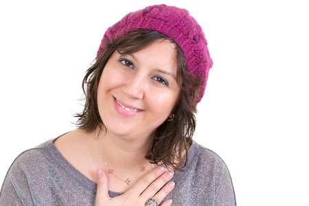 empatia: La mujer llevaba un gorro de punto púrpura muestra su sincera gratitud sosteniendo su mano en su pecho con una sonrisa sincera encantadora aislados en blanco Foto de archivo