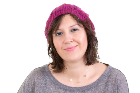 Happy attractive young woman with a charming smile wearing a purple knitted beanie, head and shoulders on white