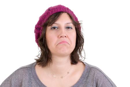 desprecio: Mujer desdeñosa Supercilious en un gorro de punto morado con desprecio a la cámara con una mirada desdeñosa, la cabeza y los hombros en blanco Foto de archivo