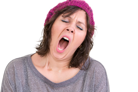 Exhausted or bored woman wearing a knitted beanie yawning with her mouth wide open and eyes shut isolated on white photo