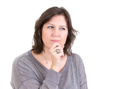 scheming: Woman with a calculating pensive look sitting with her hand to her chin as she plans and schemes for the future, isolated on white