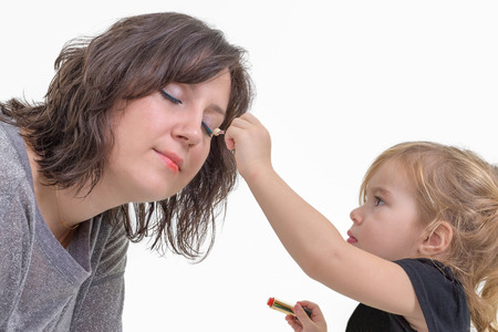 imitating: Adorable litte blond girl applying makeup to her mother putting eyeshadow on her eyes, isolated on white