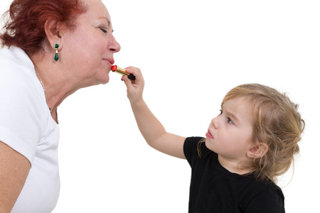 Young girl concentrates on applying lipstick to her grandmothers lips. Studio portrait over white.