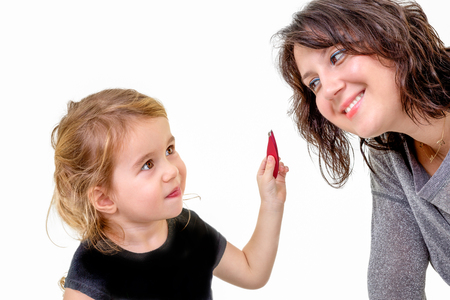 imitating: Cute little girl with a playful expression wanting to apply her mothers makeup holding it up in her hand as her mother bends forwards to oblige with a smile, isolated on white