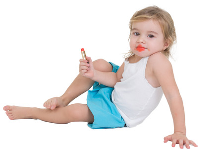imitating: Cute little girl playing with red lipstick sitting on the floor with her mouth smeared in red, isolated on white