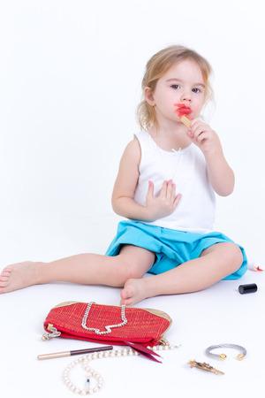 niños actuando: Adorable niña pequeña jugando con el maquillaje que se sienta en el suelo con una pequeña bolsa de cosméticos corra el lápiz labial rojo brillante en los labios