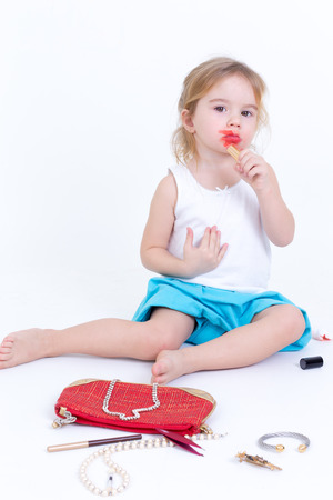 imitating: Adorable small girl playing with makeup sitting on the floor with a small bag of cosmetics smearing bright red lipstick on her lips
